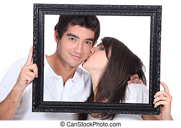 Young couple kissing in a frame