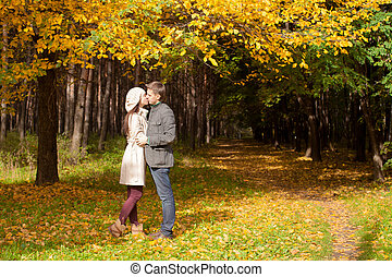 Young Couple kissing in autumn park on a sunny fall day