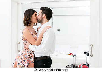 Young couple kissing in hotel suite.