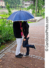 Young couple kissing in the park under umbrella