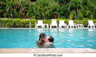 Young couple kissing in the swimming pool on their vacation. slow motion.