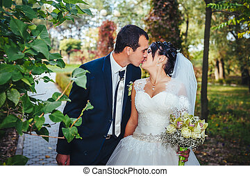 Young couple kissing in wedding gown. Bride holding bouquet of flowers
