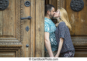 Young couple kissing near old doors