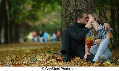 Young couple kissing on fallen leaves in autumn park