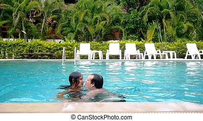 Young couple kissing, swimming and have a fun in the swimming pool. slow motion.