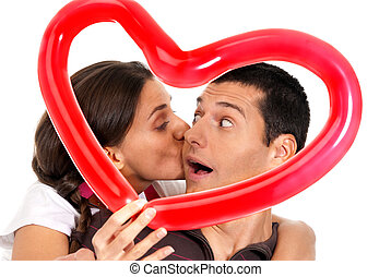 Young couple kissing through baloon heart surprise isolated