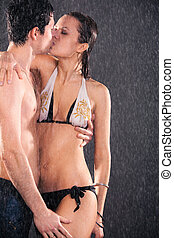 Young couple kissing. Water studio photo.