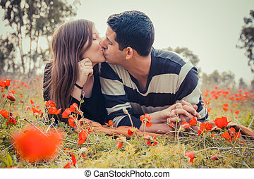 Young couple kissing while lying on the grass in a field of red poppies