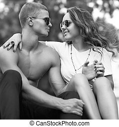 young couple kissing with sunglasses outdoors