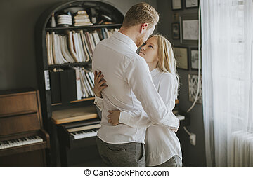 Young couple laughing, embracing and  having fun in the room