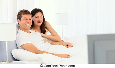 Young couple laughing in front of tv