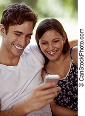 Young couple laughing with a smartphone