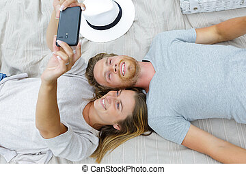 young couple laying down doing a selfie