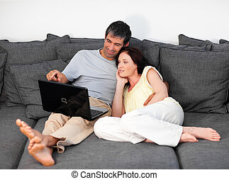 Couple laying on couch with laptop - Young Couple laying on...