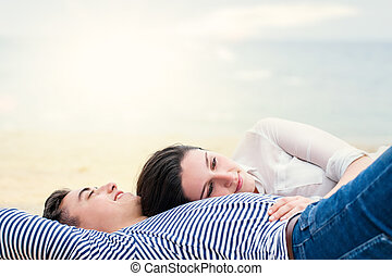 Young couple laying together outdoors.