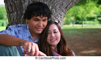 Young couple leaning against tree