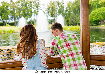 Young couple leaning on railing of the gazebo