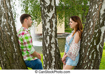 Young couple leaning on trees and looking at each other in a park