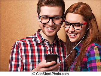 Young couple listening music together. Hipster style.
