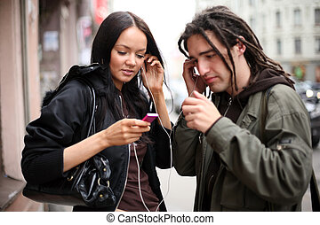 Young couple listening to a portable mp3 music player on a...
