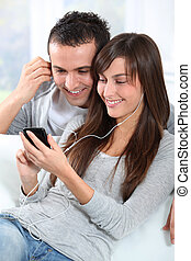 Young couple listening to music with mobile phone