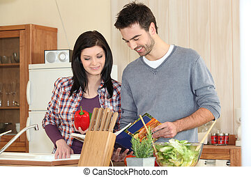 Young couple looking at a recipe book