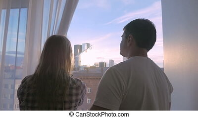 Young couple looking at big city through the window