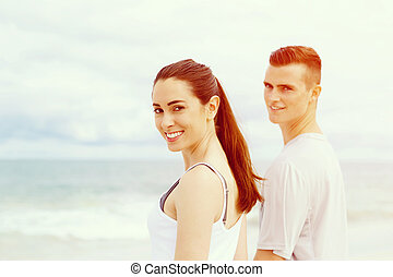 Young couple looking at camera standing on beach