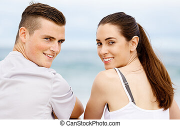 Young couple looking at camera while sitting next to each other on beach