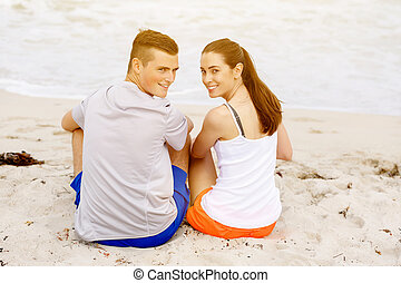 Young couple looking at camera while sitting on beach