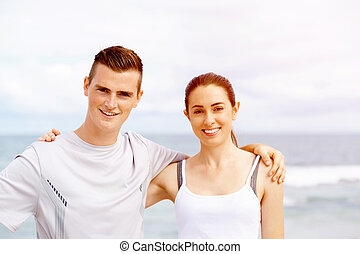 Young couple looking at camera while standing on beach