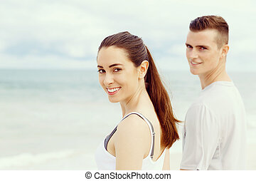 Young couple looking at camera while standing next to each other on beach