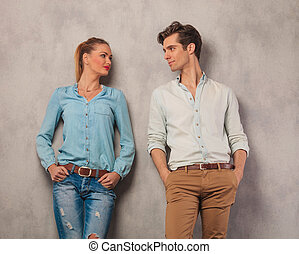 couple looking at each other with hands in pockets