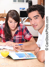 Young couple looking at holiday brochures