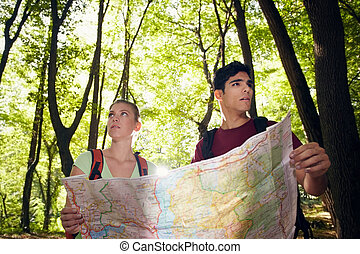 young man and woman got lost during hiking excursion and look for destination on map. Horizontal shape, waist up