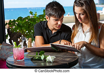 Young couple looking at menu in restaurant.
