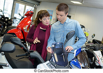 Young couple looking at modern scooter