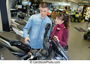 Young couple looking at scooter