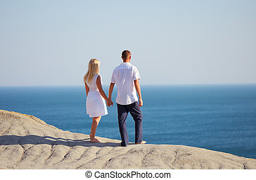 Young couple looking at the sea