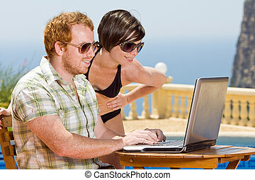 Young Couple Looking at their Laptop Whilst on Holiday