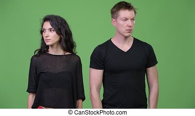 Young couple looking away from each other - Studio shot of...