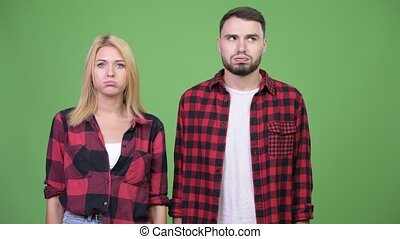 Young couple looking bored together - Studio shot of young...