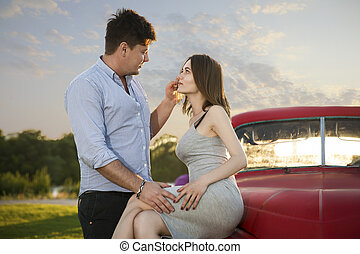 Young couple looking into each other's eyes. Romantic young couple sitting on hood of their car enjoying the moment, outdoors with copy space.