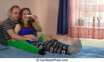 Young couple looking pregnancy test in bedroom