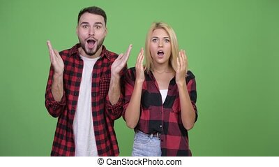 Young couple looking surprised together - Studio shot of...
