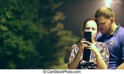 young couple looking to the smartphone night park