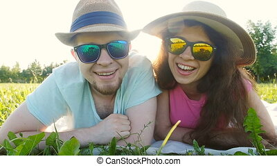 Happy young couple lying down in grass looking to camera and smiling