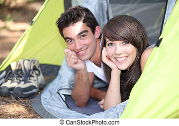 Young couple lying in a tent