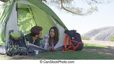 Young couple lying in tent - Two young tourists lying in...