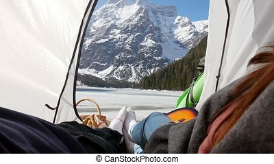 Young couple lying in the tent and holding hands. Mid shot